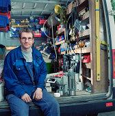Workman sitting in back of van, taking break, portrait