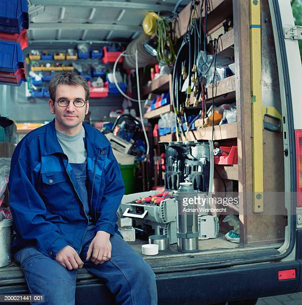 Workman sitting in back of van, taking break, portrait