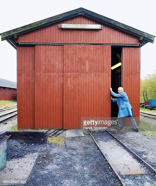 Workman sliding open workshed door in railway depot