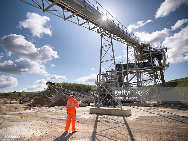 Workman standing next to stone screening and crushing machine in quarry