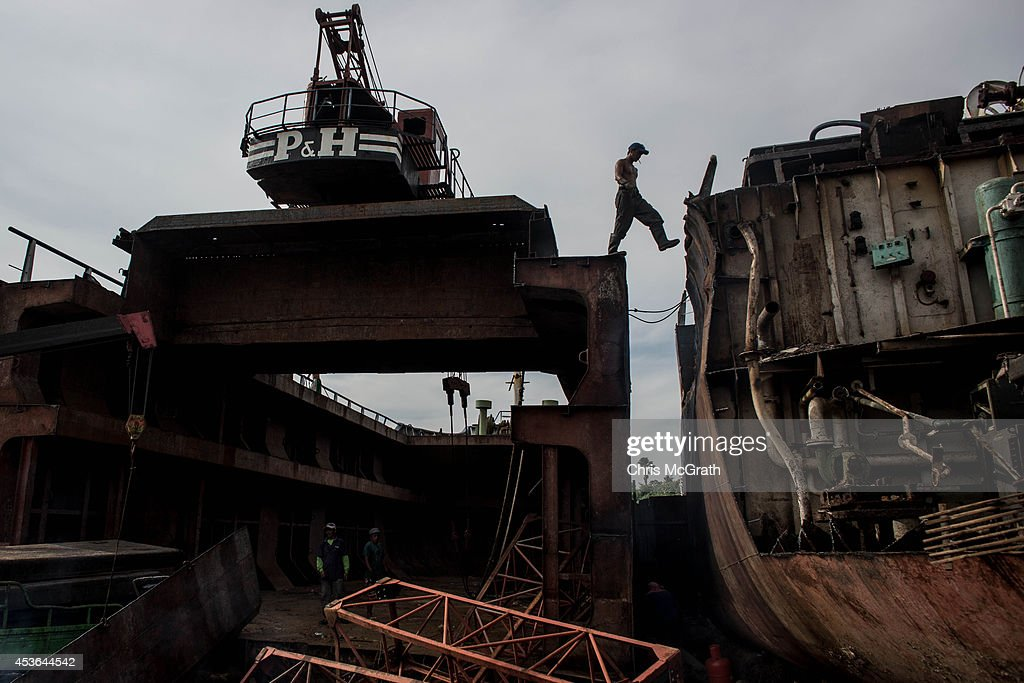 A workman steps across the decks of two large ships being broken down for scrap in the township renamed by residents as ' Yolanda Village' on August 15, 2014 in Tacloban, Leyte, Philippines. Residents of Tacloban city and the surrounding areas continue to focus on rebuilding their lives nine months after Typhoon Haiyan struck the coast on November 8, 2013, leaving more than 6000 dead and many more homeless. With many businesses and government operations back up and running and with the recent start of the years typhoon season, permanent housing continues to be the main focus with many families still living in temporary accommodation. As well as continuing recovery efforts Leyte is preparing for the arrival of Pope Francis, who will visit the region from January 15- 19.