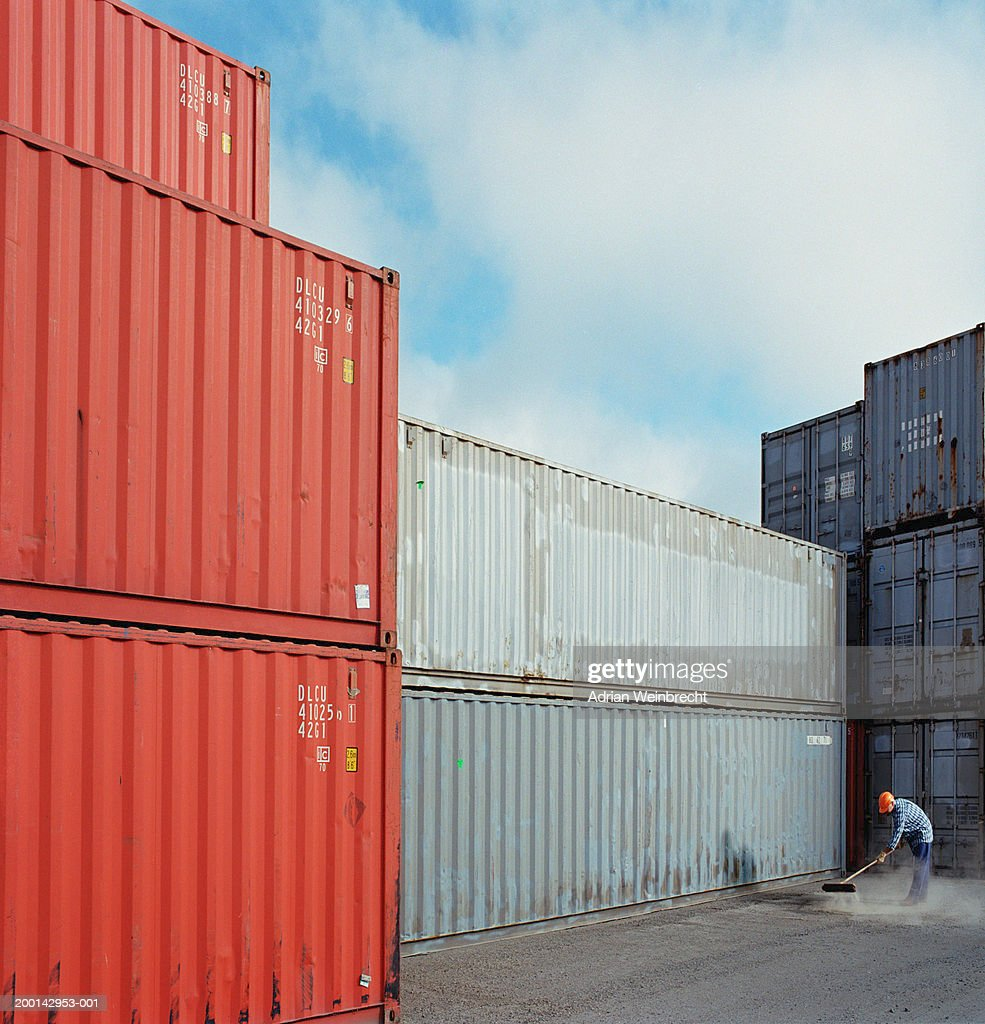 Workman Sweeping Ground In Freight Container Storage Yard : Stock Photo