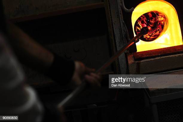A workman turns glass in a furnace on the island of Murano on September 10 2009 in Venice Italy Traditional glass making became established on the...