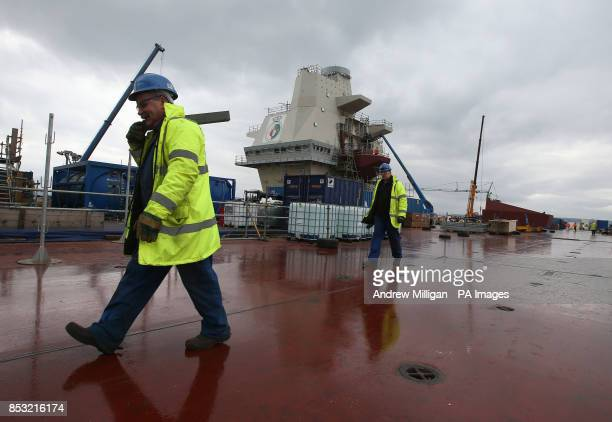 Workman walk across the flight deck as work continues on HMS Queen Elizabeth Aircraft Carrier at Rosyth Docks