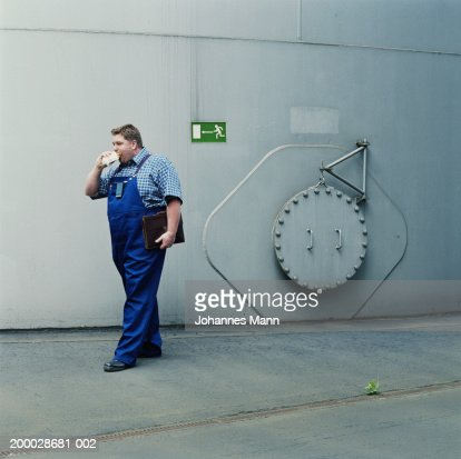 Workman walking outside power station, eating snack : Stock Photo