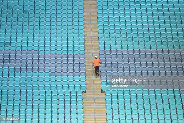 A workman walks up the stairs surrounded by empty seats as he works inside the stadium during a Queensland Maroons State of Origin captain's run at...