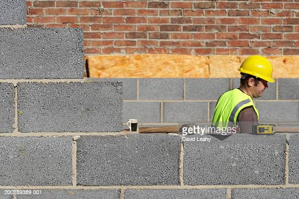 Workman wearing hard hat by wall, side view