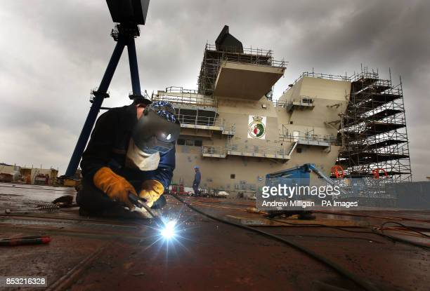 A workman welds on the runway deck of HMS Queen Elizabeth Aircraft Carrier at Rosyth Docks