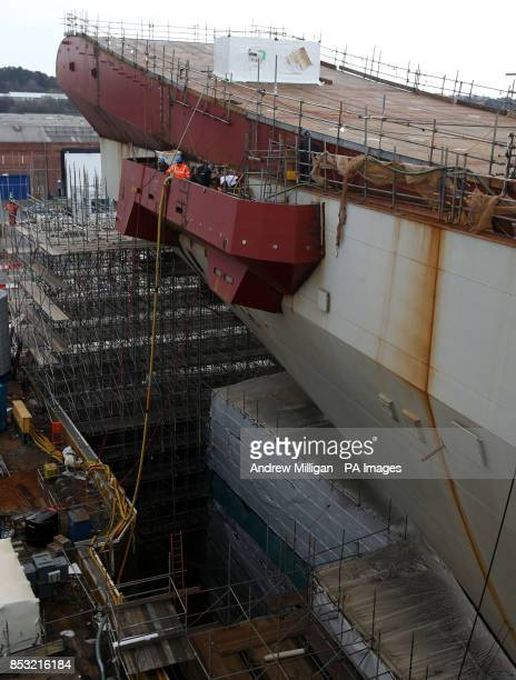 Workman work near the take off ramp on the deck as work continues on HMS Queen Elizabeth Aircraft Carrier at Rosyth Docks