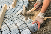 Laying paving stone, just hands in gloves and a hammer in action, hammering on the paving stones.