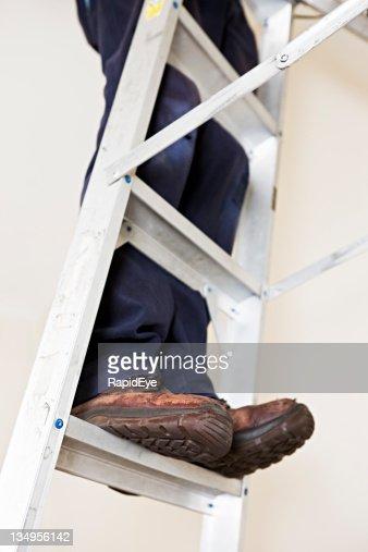 Workman's legs climb aluminum ladder