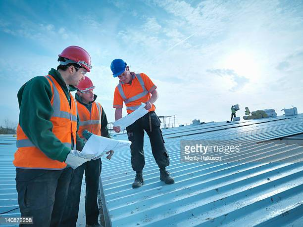 Workmen and apprentice discussing plans on factory roof