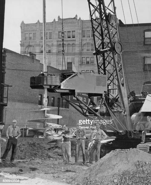 Workmen and officials look over the huge rotating drill being used to bore holes 48 feet deep for the concrete caissons to support Denver's new...