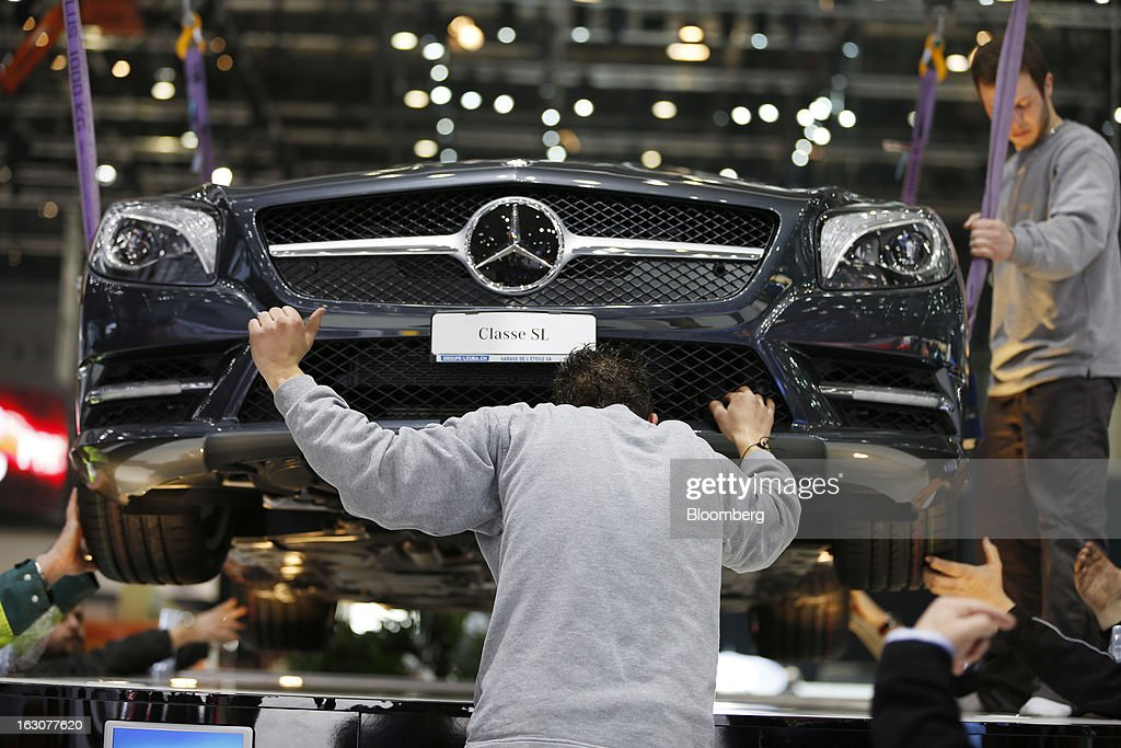 Workmen are seen lowering a Mercedes-Benz SL automobile, produced by Daimler AG, into position on the company's stand ahead of the opening day of the 83rd Geneva International Motor Show in Geneva, Switzerland, on Monday, March 4, 2013. This year's show opens to the public on Mar. 7, and is set to feature more than 100 product premiers from the world's automobile manufacturers. Photographer: Valentin Flauraud/Bloomberg via Getty Images