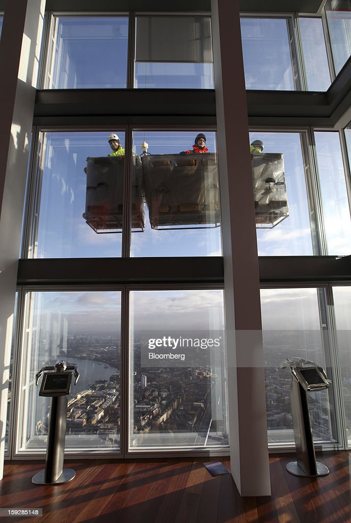 Workmen as seen moving in a mechanical lift on the exterior of the Shard tower, from 'The View From The Shard', a series of viewing galleries near the top of the tower in London, U.K., on Wednesday, Jan. 9, 2013. The Shard, which stands at 309.6 meters on London's South Bank, is owned by LBQ Ltd., which brings together the State of Qatar (the majority shareholder) and Sellar Property Group Ltd., with non-equity funding by Qatar National Bank. Photographer: Chris Ratcliffe/Bloomberg via Getty Images