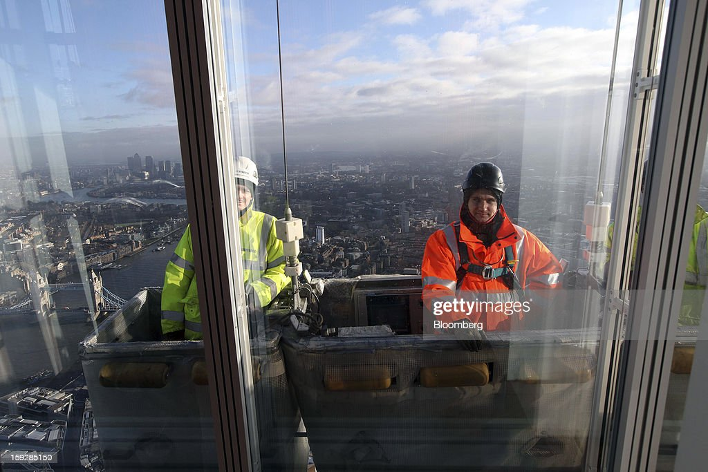 Workmen as seen moving in a mechanical lift on the exterior the Shard tower, from 'The View From The Shard', a series of viewing galleries near the top of the tower in London, U.K., on Wednesday, Jan. 9, 2013. The Shard, which stands at 309.6 meters on London's South Bank, is owned by LBQ Ltd., which brings together the State of Qatar (the majority shareholder) and Sellar Property Group Ltd., with non-equity funding by Qatar National Bank. Photographer: Chris Ratcliffe/Bloomberg via Getty Images