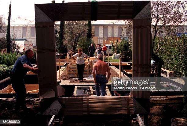 Workmen assist in the placing of a large metal frame onto the Evening Standard show garden during the build up to the Chelsea Flower Show 2000 The...