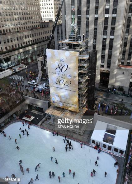 Workmen attach the Swarovski Star to the 80 foot tall Rockefeller Center Christmas Tree on November 20 2012 in New York as people skate on the ice...