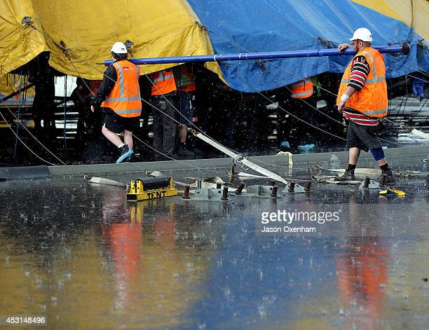 Workmen carry one of the 100 supporting poles to bring the canvas of the Cirque Du Soleil tent up during a heavy rain storm at Alexandra Park on...