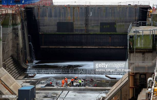Workmen carry out maintenance in a nearby dry dock as work continues on HMS Queen Elizabeth Aircraft Carrier in a nearby dock at Rosyth Docks in Fife