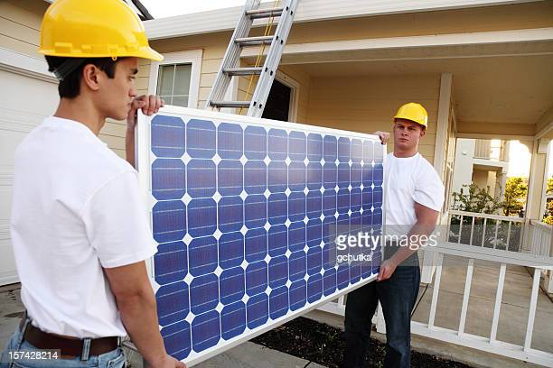 Workmen Carrying A Solar Panel
