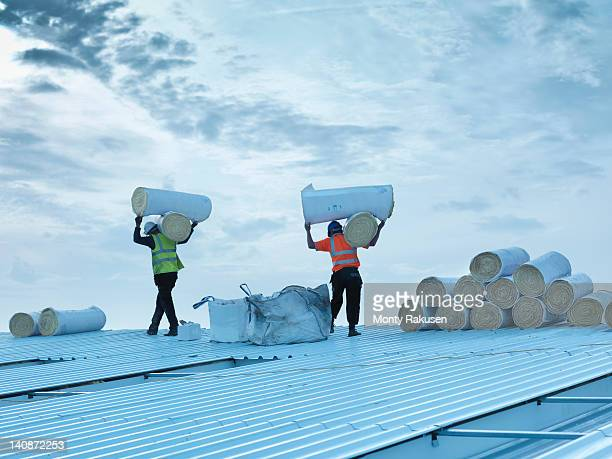 Workmen carrying rolls of insulation to install into factory roof