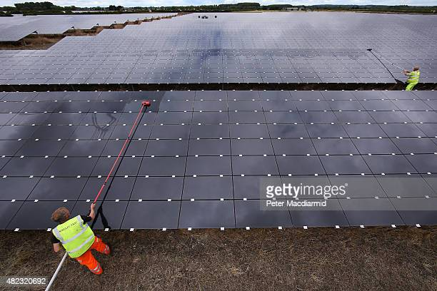 Workmen clean panels at Landmead solar farm on July 29 2015 near Abingdon England The 46 megawatt capacity installation was the largest in the United...