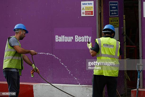 Workmen clean the sidewalk at the entrance to a Balfour Beatty Plc construction site in the King's Cross district of London UK on Friday July 25 2014...