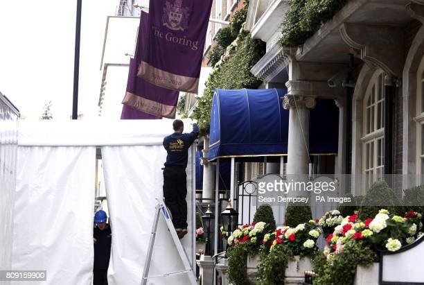 Workmen erect a screen outside the entrance to The Goring hotel which Kate Middleton has chosen as a base for herself and her closest family ahead of...