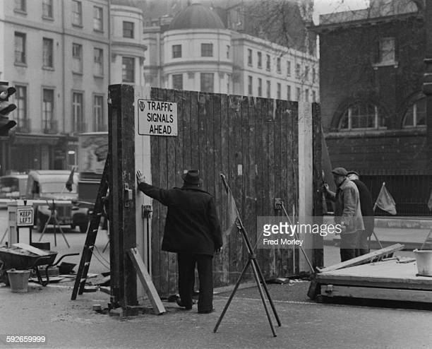 Workmen erecting a traffic barrier at the entrance to the Royal Mews for when Queen Elizabeth II and the Duke of Edinburgh return from their tour of...