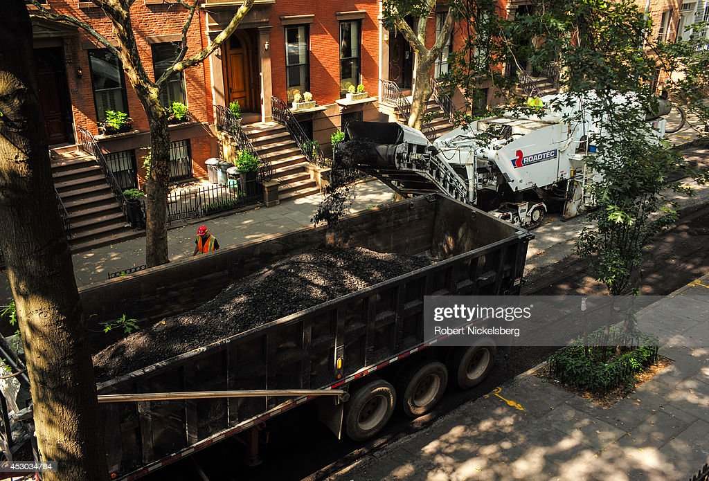 Workmen from a road construction crew guide a road milling machine July 21, 2014 down a street in the Brooklyn borough of New York City. The work prepares a road for repaving.