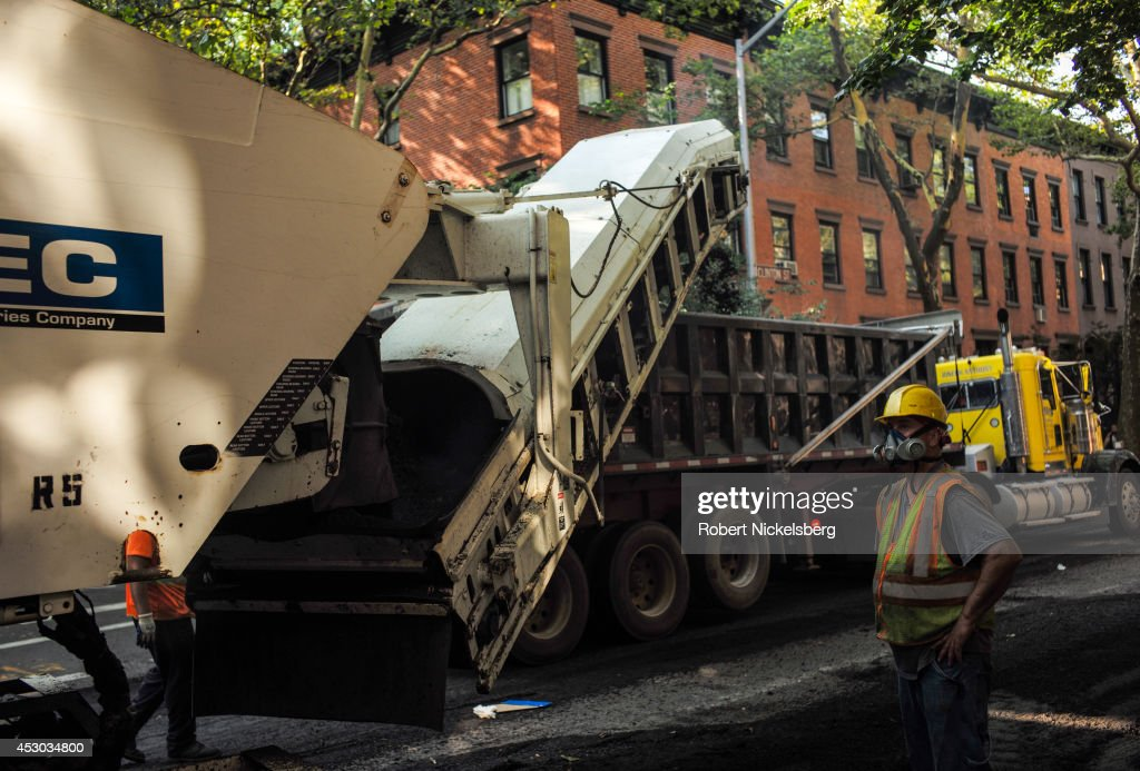 Workmen from a road construction crew guide a road milling machine July 22, 2014 down a street in the Brooklyn borough of New York City. The work prepares a road for repaving.
