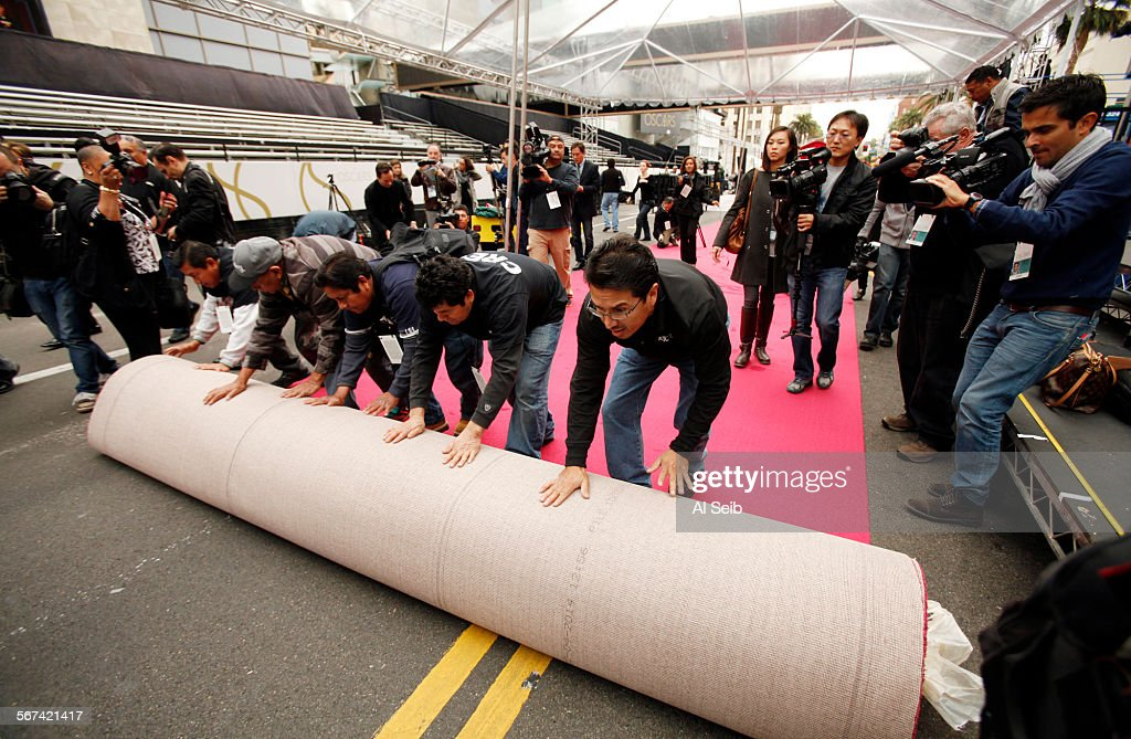 Workmen from American Turf and Carpet roll out the red carpet under a canopy on Hollywood Blvd in front of the Dolby Theater at Hollywood and...