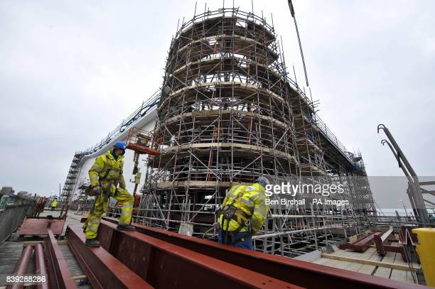 Workmen in front of the North Western corner tower which is still under construction as they prepare steel girders to be craned into position as work...