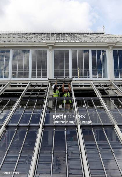 Workmen in the Royal Botanic Gardens in Kew SW London adjust the windows on the Temperate House that will reopen in May next year after the...