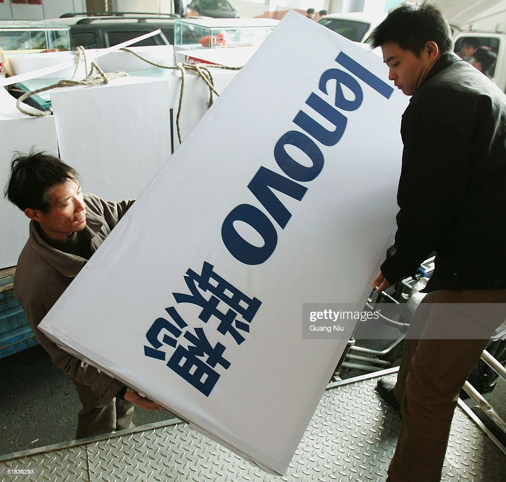 Workmen load a poster poster advertising China's largest personal computer maker Lenovo Group Ltd to be installed at a computer market on December 8...