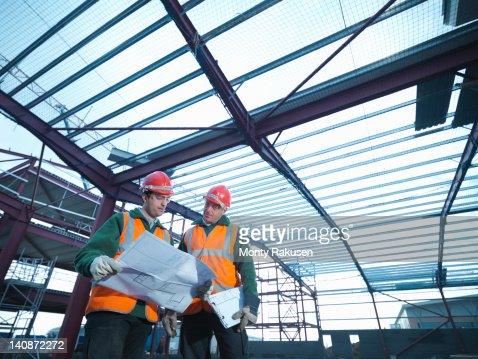 Workmen looking at plans beneath steel construction frame on building site : Foto stock