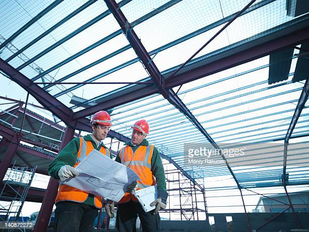 Workmen looking at plans beneath steel construction frame on building site