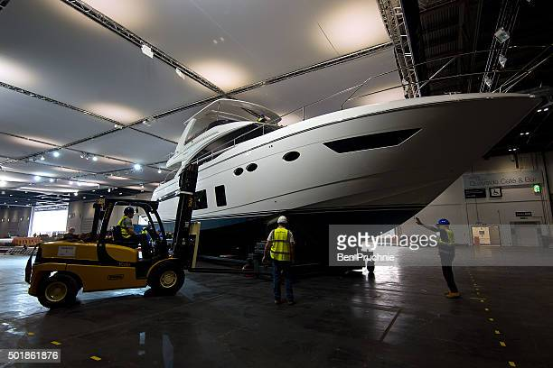 Workmen move a boat into position so it can be displayed at the London Boat Show at ExCel on December 18 2015 in London England The London Boat Show...