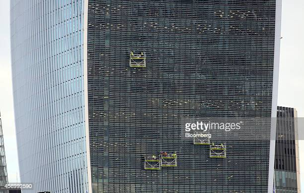 Workmen operate cradles as they work on the exterior of 20 Fenchurch Street also known as the 'WalkieTalkie' in London UK on Friday Oct 10 2014...