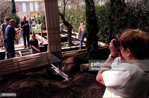 Workmen oversee the placing of a large metal frame onto the Evening Standard show garden during the build up to the Chelsea Flower Show 2000 The...