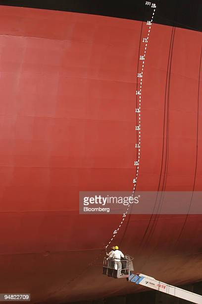 Workmen paint the forward draught marks on the towering hull of the China Peace a Hong Kongregistered 175000dwt Capesize bulk carrier in the dry dock...