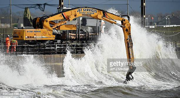 Workmen place large rocks in the sea to bolster flood defences along the sea wall on November 13 2015 in Saltcoats Scotland Storm Abigail has closed...