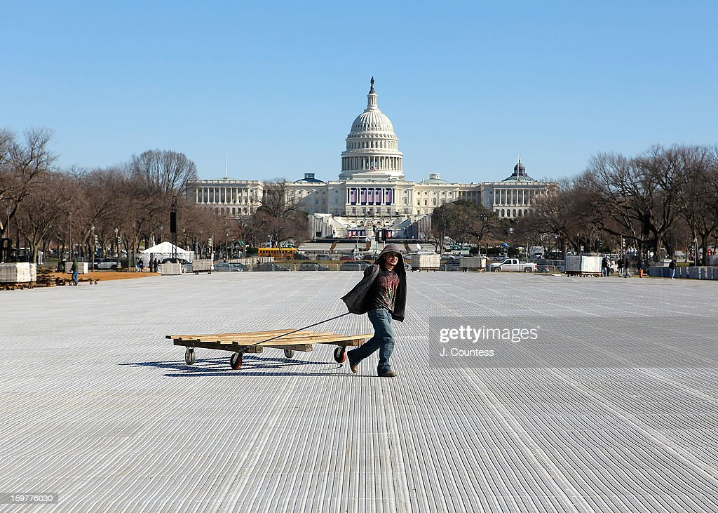 Workmen pulls a cart that contained pieces of the protective covering that is used to cover the grasses of the National Mall in preperation for the 57th United States Presidential Inauguration on January 18, 2013 in Washington, United States.