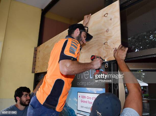 Workmen put up plywood panels to protect a shop on the Strand as residents prepare for Cyclone Debbie on March 27 2017 in Townsville Australia...