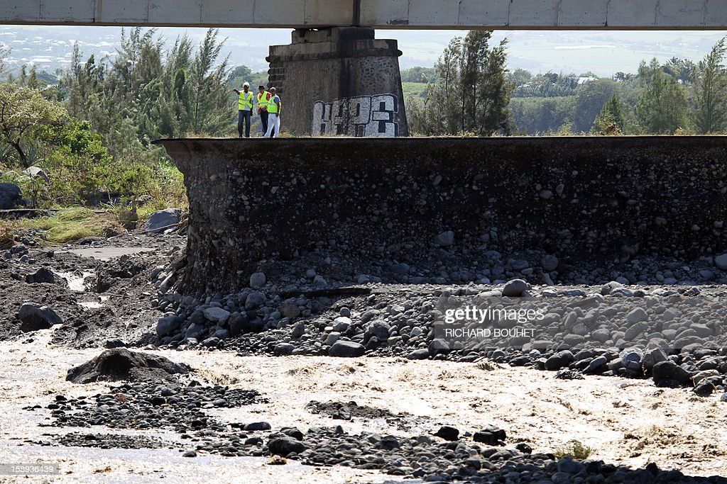 Workmen stand on a remaining piece of road crossing the river that links Saint Louis de la Reunion with Saint Pierre on January 4, 2013 near Saint Louis, on the French island of La Reunion, following the passing of cyclone Dumile. Winds of up to 180 kilometres per hour (110 miles per hour) and torrential rain caused extensive damage to the electricity network after cyclone Dumile passed within 90 kilometres of the island's west coast at around 0900 GMT. AFP PHOTO / RICHARD BOUHET