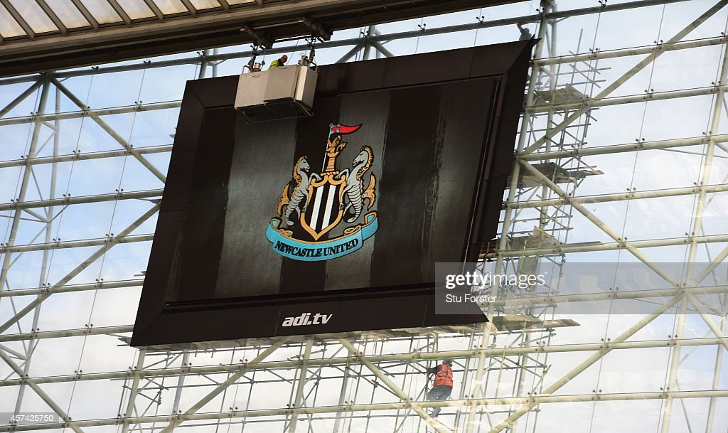 Workmen start working on fixing The new TV Screen which flaps in the wind delaying the opening of the turnstilles before the Barclays Premier League match between Newcastle United and Leicester City at St James' Park on October 18, 2014 in Newcastle upon Tyne, England.