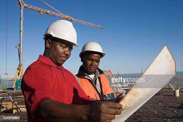 Workmen enquête des plans de bâtiment