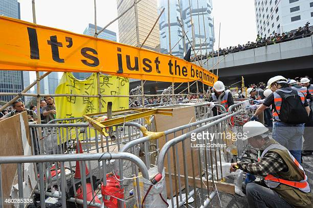 Workmen take down a barricade put up by prodemocracy protesters promising that 'It's just the beginning' under the supervision of bailiffs following...