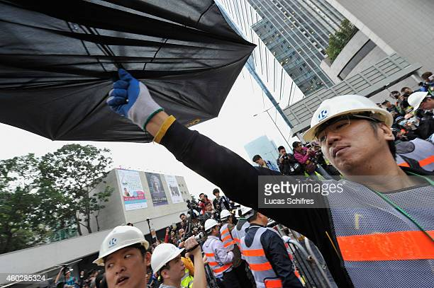 Workmen take down barricades put up by prodemocracy protesters under the supervision of bailiffs following a court injuction December 11 2014 in Hong...